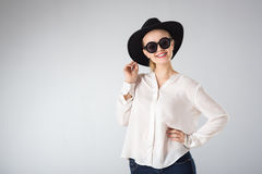 Young woman in white shirt,  glasses and hat Stock Images