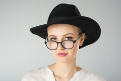 Young woman in white shirt,  glasses and hat Stock Photos