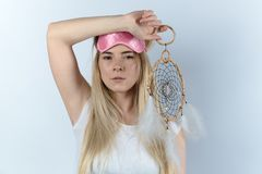 Young woman in white shirt going sleep in a sleep mask and dream. Catcher in hand. Portrait on white background, expressive look at the camera Royalty Free Stock Images