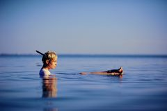 Young woman in white shirt lie on back and relaxing in blue sea water fashion shot Royalty Free Stock Photo