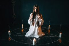 Woman sitting in the center of pentagram circle. Young woman in white shirt sitting in the center of pentagram circle with candles and reads a spell, black Stock Image