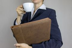Young woman in white shirt and suit holding a cup of coffee and leather folder in her hands. Business concept royalty free stock image
