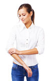 Young woman in white shirt turning up sleeves Royalty Free Stock Photos