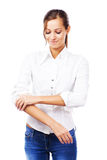 Young woman in white shirt turning up sleeves Stock Image