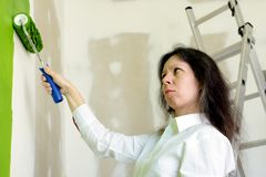Young woman in white shirt upset with a green color of a painted wall stock image