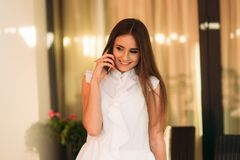 Young woman in white shirt use phone and smile. Happy attrective girl stock photography