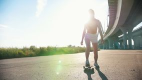 Young woman in white shorts with nice legs riding skateboard under the urban bridge - bright sunlight. Mid shot stock video footage