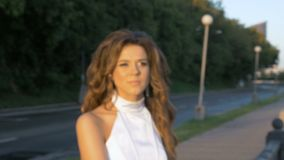 A young woman in a white suit is standing on the city embankment. Motion the camera out of focus to focus. stock video footage