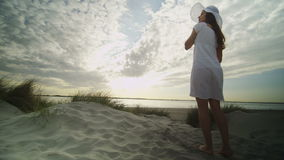 Young woman in a white summer dress and hat walks up a sandy bank to enjoy the sea view, in slow motion stock footage