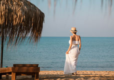 Young woman in a white sundress and hat  walking near the sea Stock Images