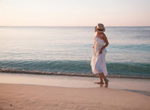Young woman in a white sundress walking along seashore Royalty Free Stock Photo