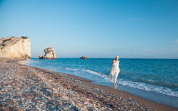 Young woman in white sundress walking along the seashore Stock Images