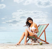 A young woman in a white swimsuit adding suntan cream Royalty Free Stock Image