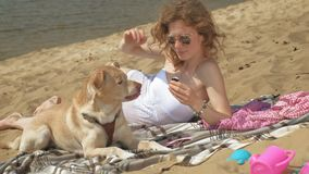 A young woman on the bank of the river is eating ice cream. Outdoor recreation. A young woman in a white swimsuit  lying on the sand on the bank of the river are stock video