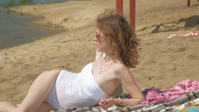A young woman on the bank of the river is eating ice cream. Outdoor recreation. A young woman in a white swimsuit  lying on the sand on the bank of the river are stock video footage