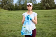 Young woman in white t shirt and baseball cap holding blue garbage bag in hands, female collecting litter in meadow, looks at