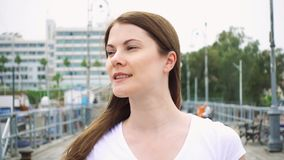 Young woman in white t-shirt walking on pier alone. Wind from sea blowing female hair in slow motion stock video footage