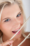 Young woman with white teeth and pearls Royalty Free Stock Image