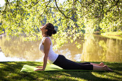 Young woman in white top practicing yoga in beautiful nature. Meditation in morning sunny day.  Royalty Free Stock Photo