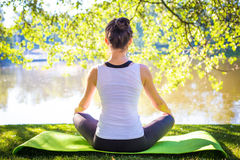 Young woman in white top practicing yoga in beautiful nature. Meditation in morning sunny day.  Royalty Free Stock Photos