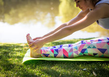 Young woman in white top practicing yoga in beautiful nature. Meditation in morning sunny day.  Royalty Free Stock Image