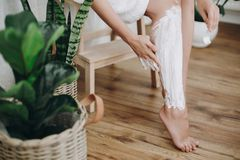 Young woman in white towel applying shaving cream on her legs in home bathroom with green plants. Skin care and wellness concept. Hand smearing moisturizer royalty free stock photo