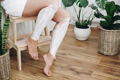 Young woman in white towel applying shaving cream on her legs in home bathroom with green plants. Skin care and wellness. Hair. Removal concept, depilation royalty free stock images