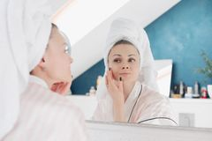 Young woman looking at camera and applying cream on face stock photos