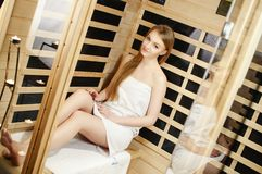 Young woman in white towel resting in sauna Royalty Free Stock Images