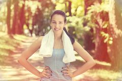 Young woman with white towel resting after workout. Portrait young attractive smiling fit woman with white towel resting after workout sport exercises outdoors Stock Image