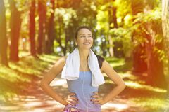 Young woman with white towel resting after workout. Portrait young attractive smiling fit woman with white towel resting after workout sport exercises outdoors Royalty Free Stock Photography