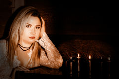 Young woman in white transparent dress stending near black candels, divination and black magic concept Stock Photos