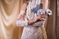 Woman in white vintage style dress. female hand hold carnival ma. Young woman in white vintage style dress. female hand hold carnival mask. retro masquerade Stock Image