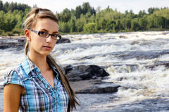 Young woman and white waters. Young friendly brunette looking at camera in front of beautiful white waters waterfall landscape Stock Image