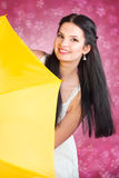 Young woman in white with a yellow umbrella. Рortrait of a dark-haired young woman in a white dress with a yellow umbrellaPortrait of a young dark-haired woman Stock Image