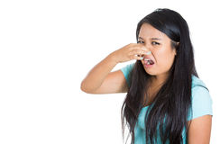 Young woman who covers her nose, looks away, something stinks, very bad smell, situation Royalty Free Stock Images