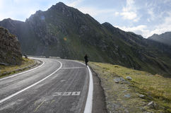 Young woman who goes on a mountain road. Mountain road and a young woman Royalty Free Stock Photo