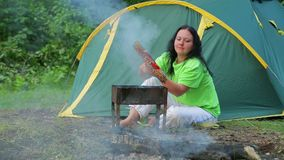 A young woman who sits in a forest on the background of a tent turns over a barbecue on her barbecue. stock video