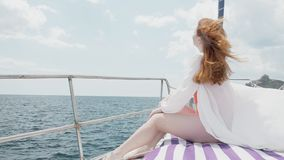 Bright and warm scene with a red-haired young woman who smiles at you She is sitting on the bow of a yacht that cuts