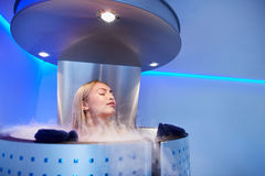 Young woman in a whole body cryo sauna Royalty Free Stock Image