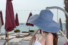 Young woman in a wide brimmed blue straw sunhat Stock Photography