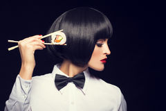 Young woman with wig holding sushi Royalty Free Stock Images