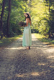 Young woman with wild flowers on a country road Royalty Free Stock Photo