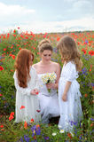 Young woman with wild flowers and cute girls in the blooming spr. The young women with wild flowers and cute girls in the blooming spring poppy. Mothers day Royalty Free Stock Photo