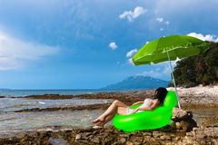 Young woman on wild island beach resting. Under umbrella, facing the sea. Croatia, Losinj coast Stock Images