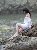 Young woman on wild rocky seashore Stock Image