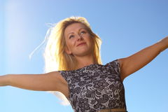 Young woman wind in hair outdoor outstretched arms Royalty Free Stock Image