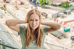 A young woman by the window annoyed by the building works outside. Noise concept.  stock image