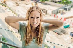 A young woman by the window annoyed by the building works outside. Noise concept.  stock images