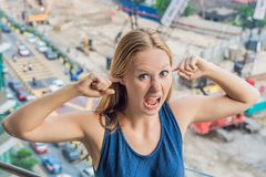 A young woman by the window annoyed by the building works outside. Noise concept.  stock photos